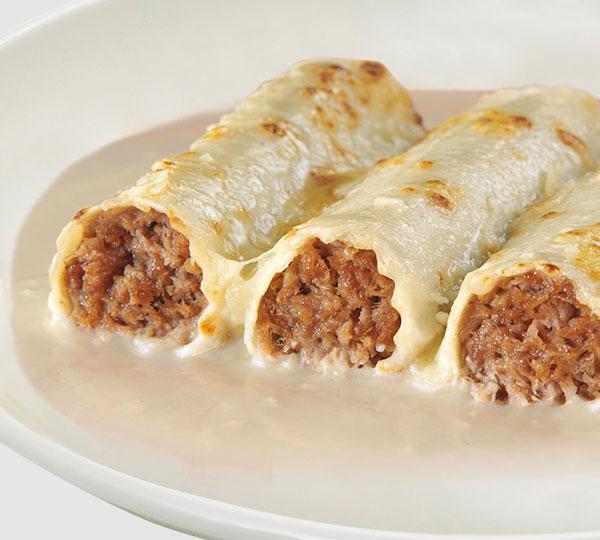 Canelons de carn-Típiques porcions de pasta enrotllada, farcides amb carn guisada i triturada. Cobertes amb salsa beixamel i formatge.