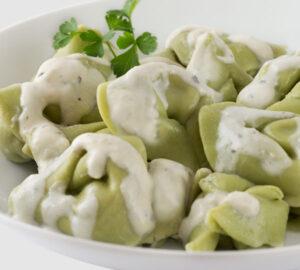 Tortellini ricotta y espinacas Pasta de espinacas rellena de ricotta con salsa de finas hierbas y queso.