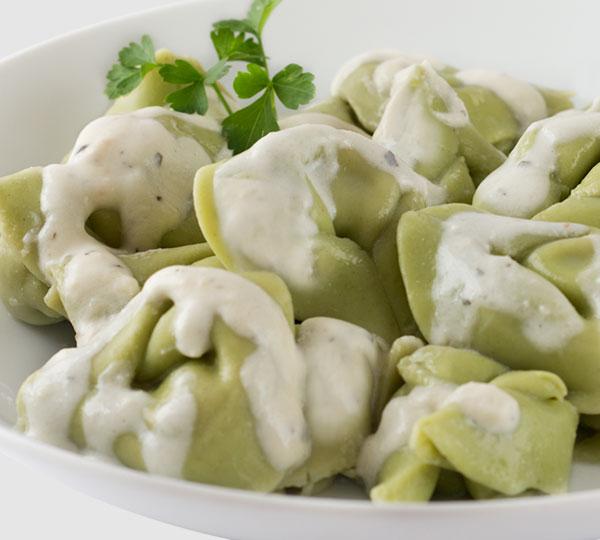 Tortellini ricotta i espinacs-Pasta d'espinacs farcida de ricotta amb salsa de fines herbes i formatge.